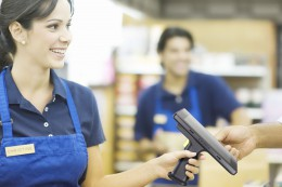 Closeup of a hand giving female employee loyalty card in supermarket